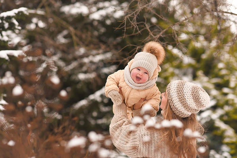 Mutter spielt mit niedlichen Baby Junge auf dem Schnee