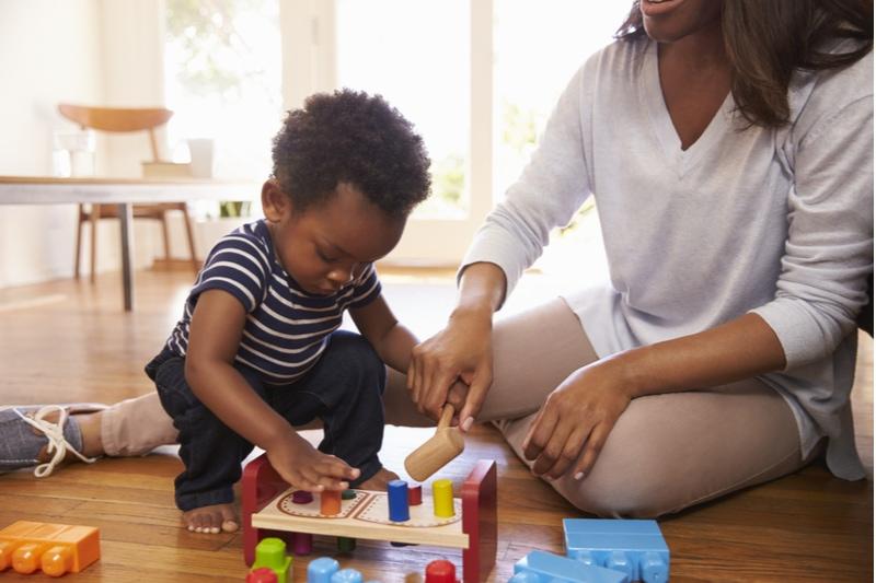Mutter und Sohn spielen mit Spielzeug auf dem Boden zu Hause