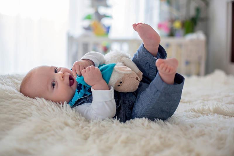 Nettes Baby Junge spielt mit Spielzeug auf dem Bett