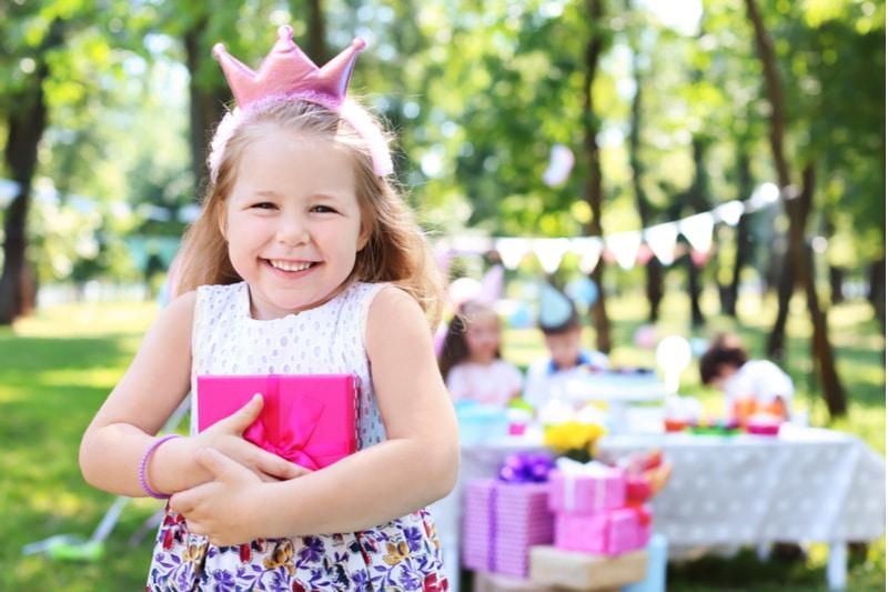 Nettes kleines Mädchen mit Geschenkbox bei Geburtstagsfeier im Freien