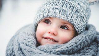 kleines Mädchen steht im Schnee und trägt eine Wintermütze und Schal