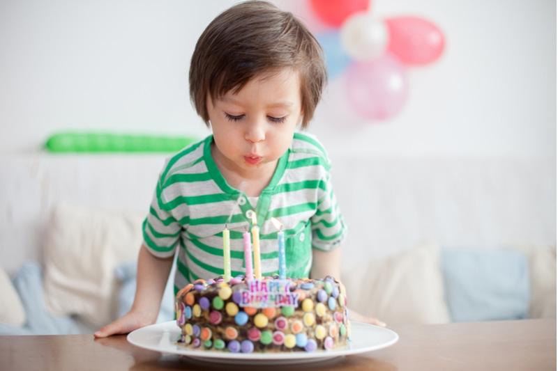 Schöner entzückender vierjähriger Junge im grünen Hemd, der seinen Geburtstag feiert
