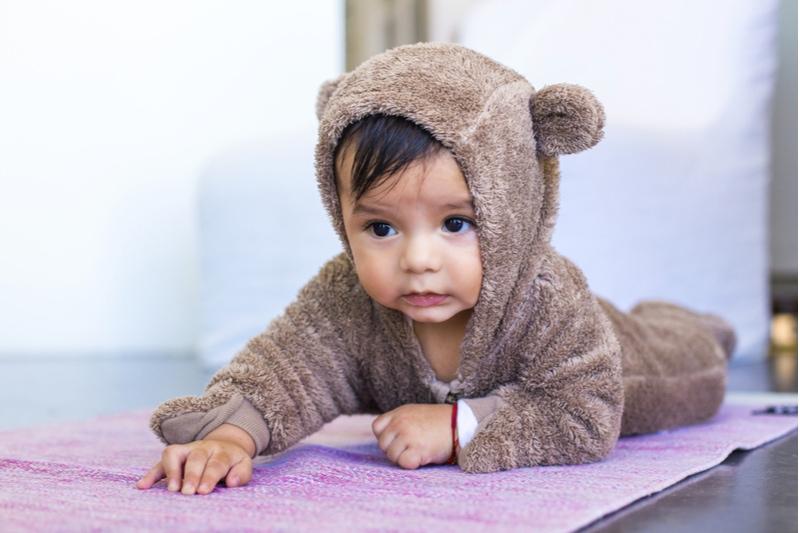 Sechs Monate mexikanischer Junge kriecht auf einem Bärenkostüm