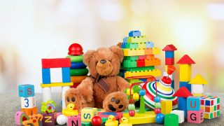 buntes Kinderspielzeug auf dem Holztisch mit Teddybär in der Mitte