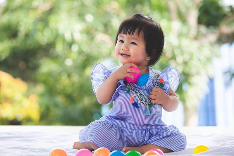 Süßes Baby Mädchen spielt mit bunten Ball Spielzeug
