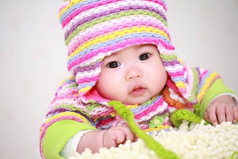 Süßes Baby trägt bunte Winter-Strickmütze