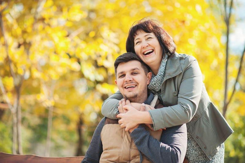eine ältere Frau, die ihren Schwiegersohn im Freien umarmt