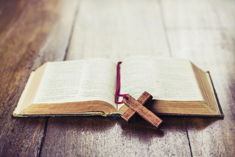 Holzkreuz über geöffnete Bibel