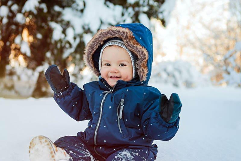 glücklich Baby Junge sitzt auf dem Schnee