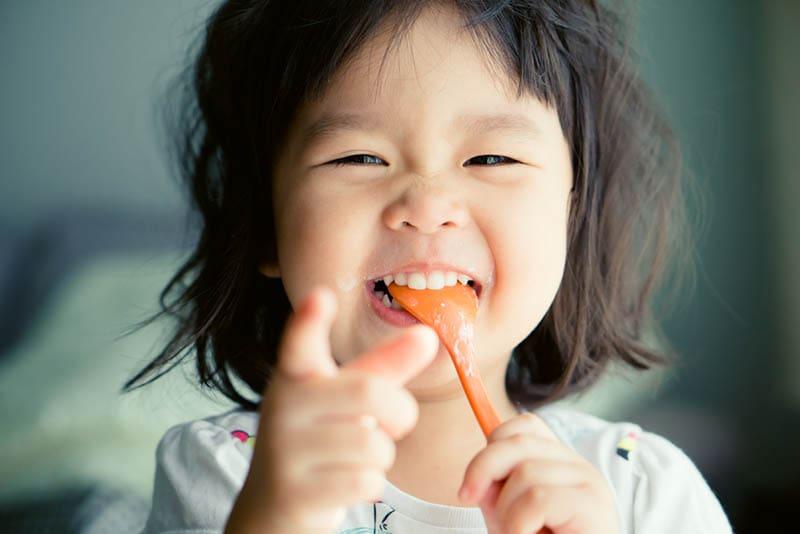 glücklich asiatische Mädchen miling mit Löffel im Mund