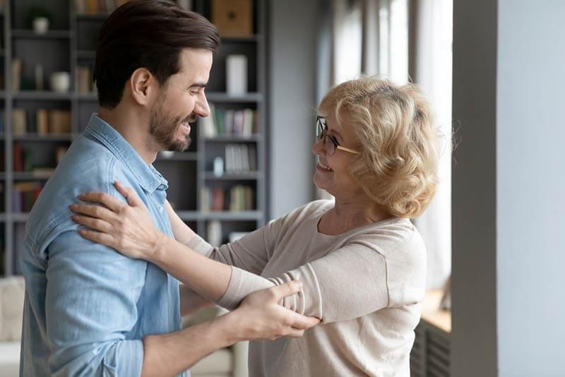 glückliche Frau umarmt Schwiegersohn zu Hause