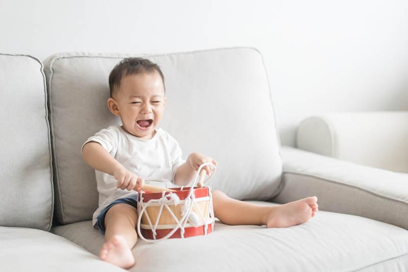 glücklicher kleiner Junge spielt Schlagzeug auf der Couch