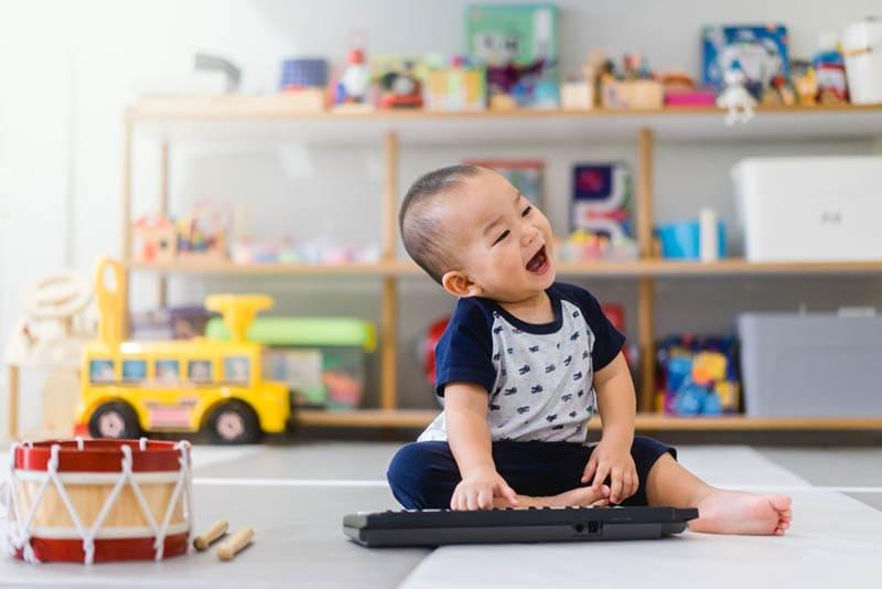 glücklicher kleiner Junge spielt mit Spielzeug auf dem Boden
