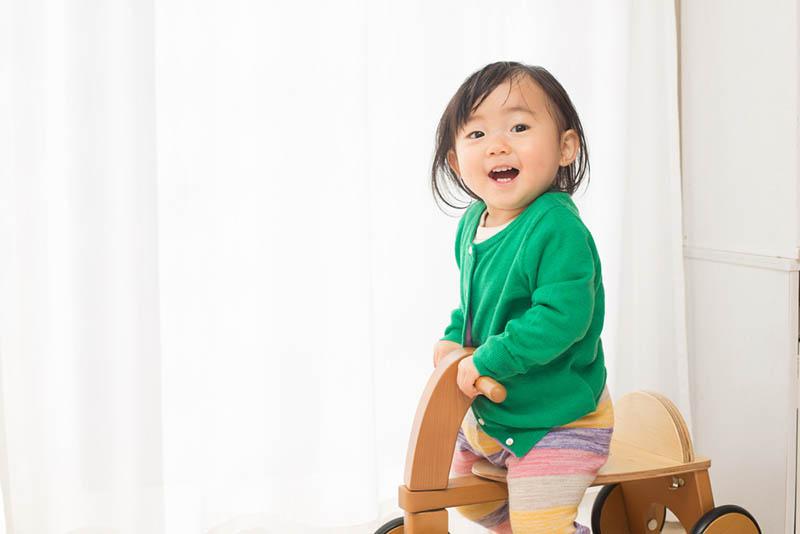 glückliches kleines Mädchen spielt auf dem Holzpferd Spielzeug