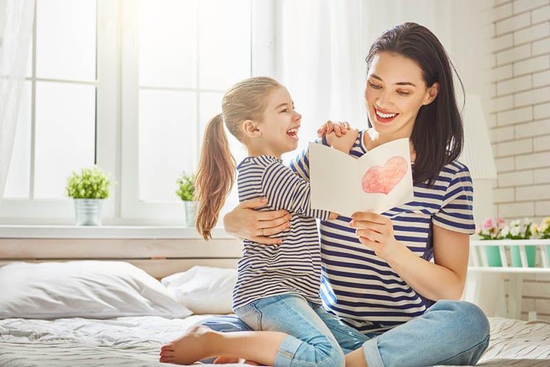 junge Mutter liest Brief von ihrer Tochter auf dem Bett