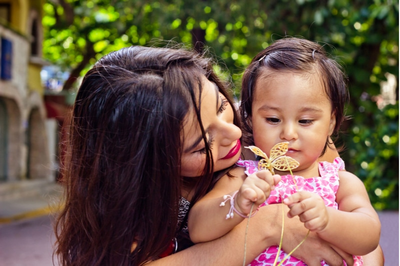 junge mexikanische Mutter hält ihre Tochter ein Spiel mit einer Plastikblume auf der Straße
