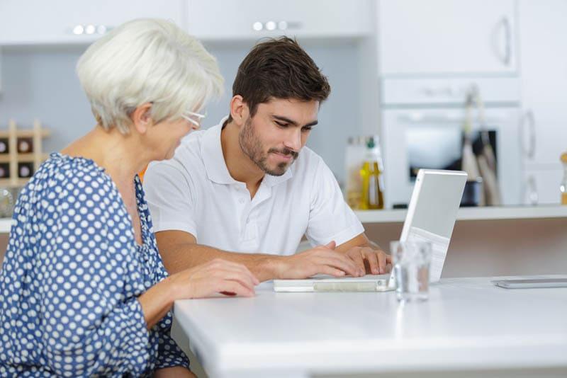 junger Mann tippt auf Laptop mit seiner Schwiegermutter