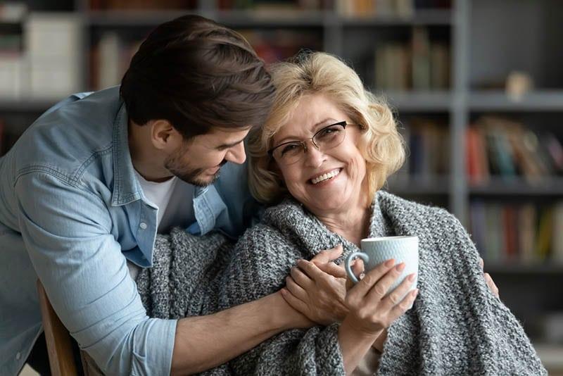 junger Mann umarmt seine Schwiegermutter zu Hause