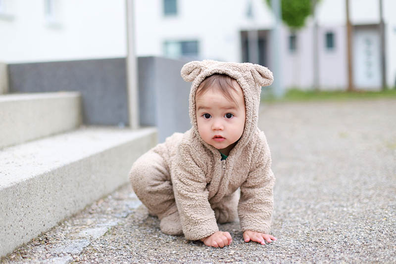 kleiner Baby-Junge im Teddybär-Kostüm im Freien