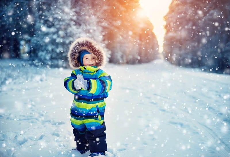 kleiner Junge im Winteranzug spielt auf dem Schnee