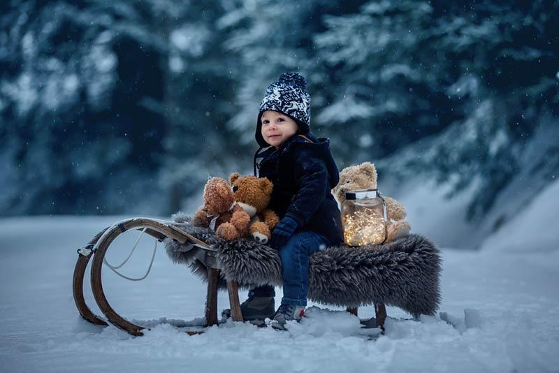 kleiner Junge sitzt auf Schlitten mit Teddybär im Schnee