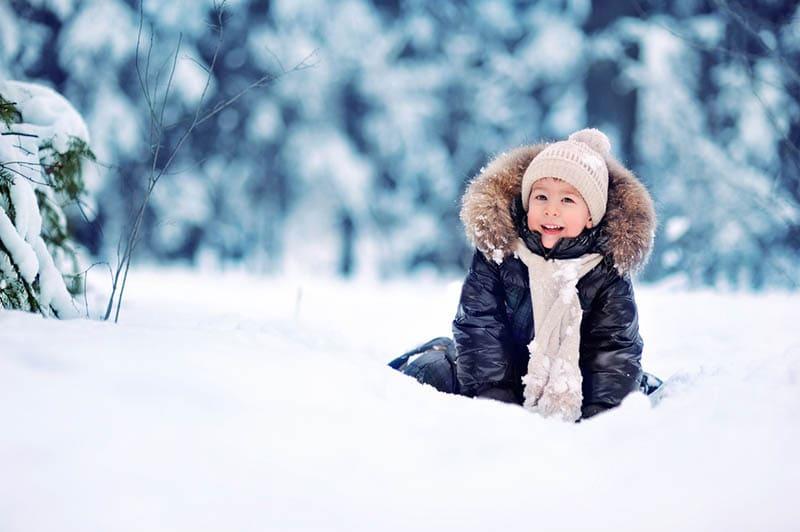 kleiner Junge sitzt im Schnee draußen im Wald