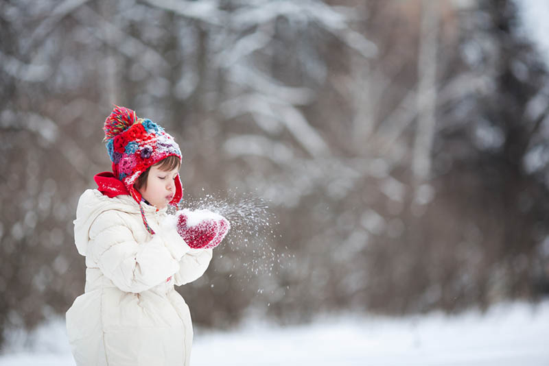 kleines Mädchen bläst den Schnee aus den Händen