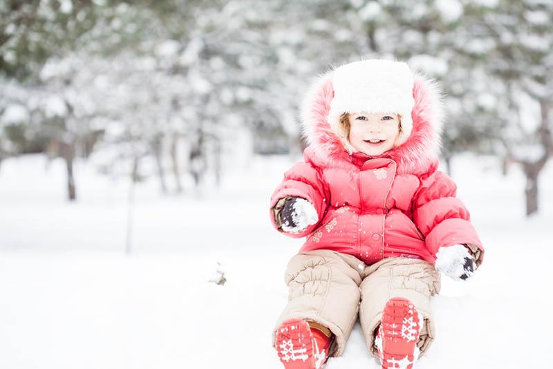 kleines Mädchen hält einen Schneeball draußen im Wald