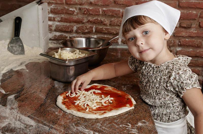 kleines Mädchen macht eine Pizza in der professionellen Küche