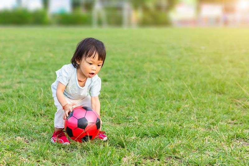 kleines Mädchen spielt mit Ball auf dem Gras im Freien