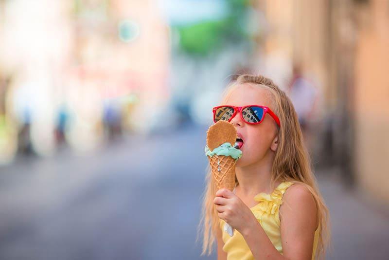 kleines blondes Mädchen isst ein Eis auf der Straße