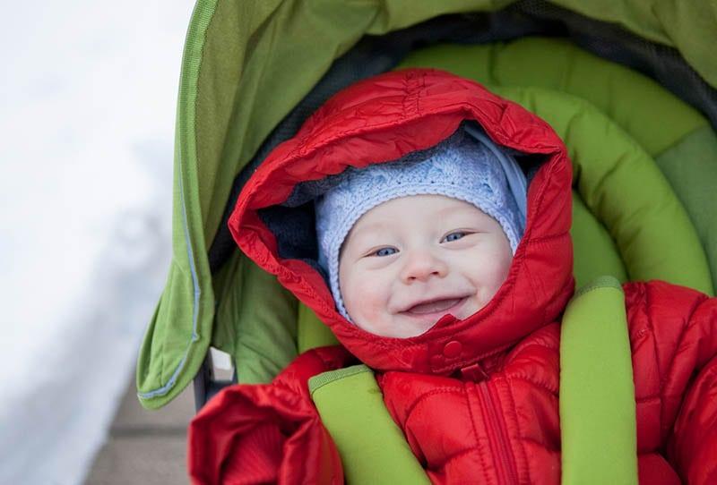 lächelnd kleiner Junge in Winterjacke sitzt in einem Kinderwagen