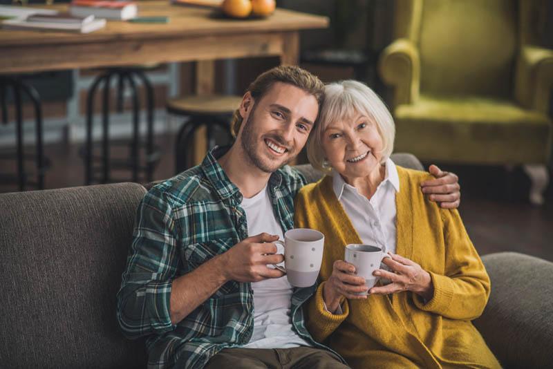 lächelnder Mann sitzt mit älterer Frau und hält Tassen mit Kaffee