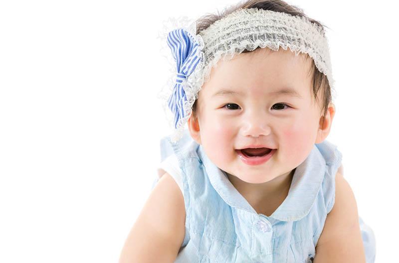 lächelndes Baby Mädchen mit Stirnband krabbelnd