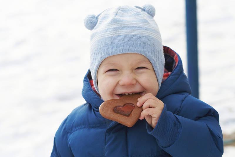 lächelndes Baby, das einen Keks in Herzform isst