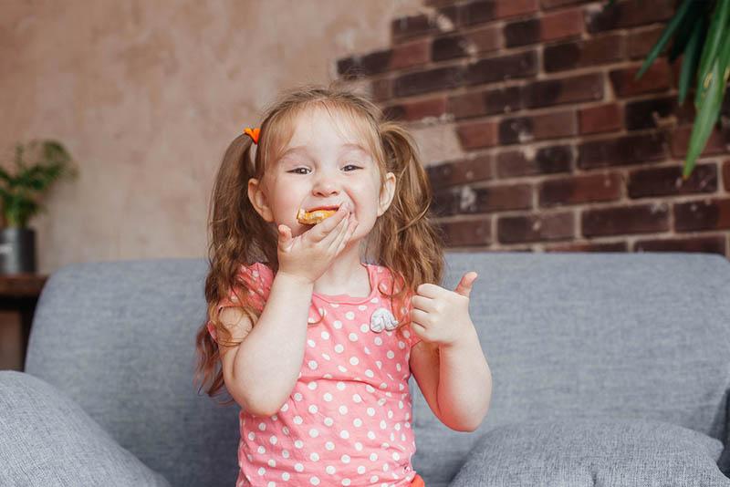 lächelndes kleines Mädchen sitzt auf der Couch und isst Pizza