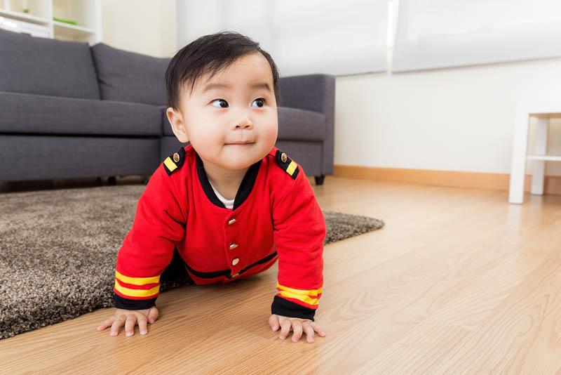 neugieriges Baby Junge krabbeln auf dem Boden
