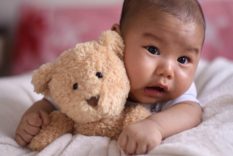 niedlichen Baby Bos auf dem Bett liegend mit Teddybär Spielzeug