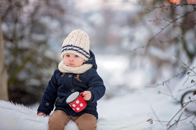 niedlichen Baby Junge hält eine Tasse auf dem Schnee