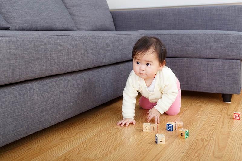 niedlichen Baby Mädchen spielen auf dem Boden mit Würfeln