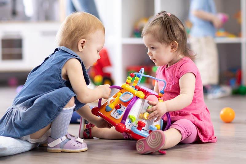 niedlichen Baby Mädchen spielen mit Spielzeug auf dem Boden