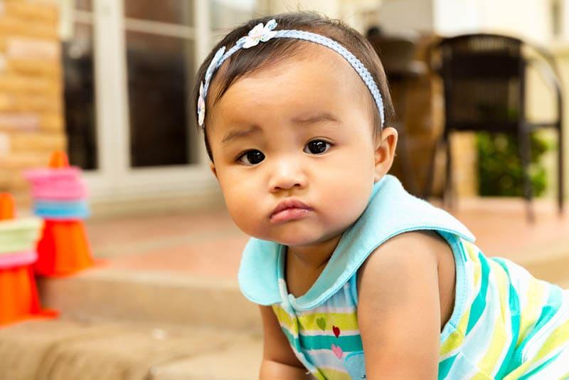 niedlichen ernsten Baby Blick auf die Kamera auf dem Boden