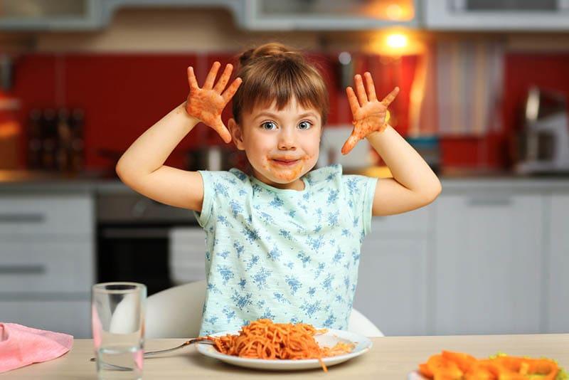 niedlichen kleinen Mädchen essen Spaghetti zu Hause