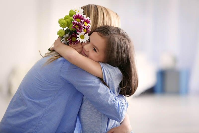 niedlichen kleinen Mädchen umarmt Mutter und geben ihr Blumen