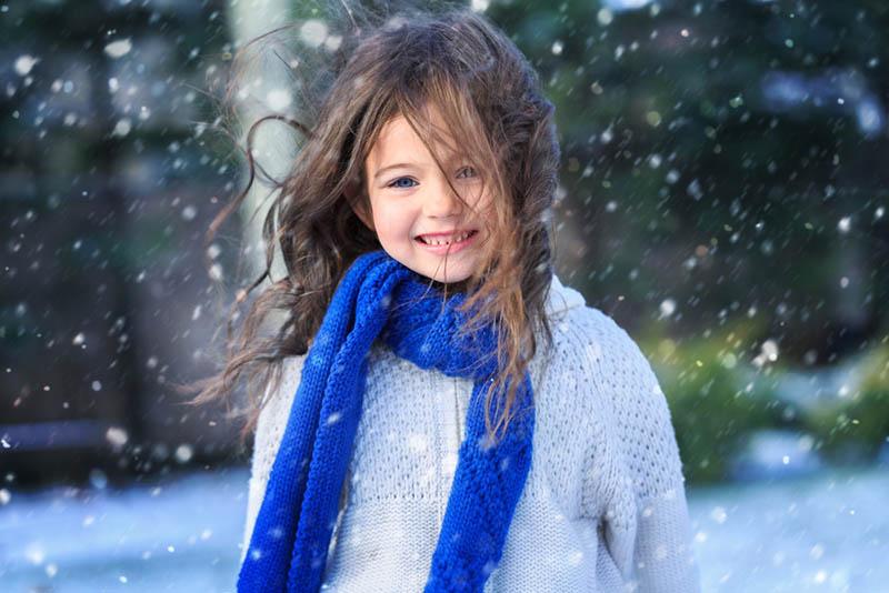 schönes kleines Mädchen auf dem Schnee stehend