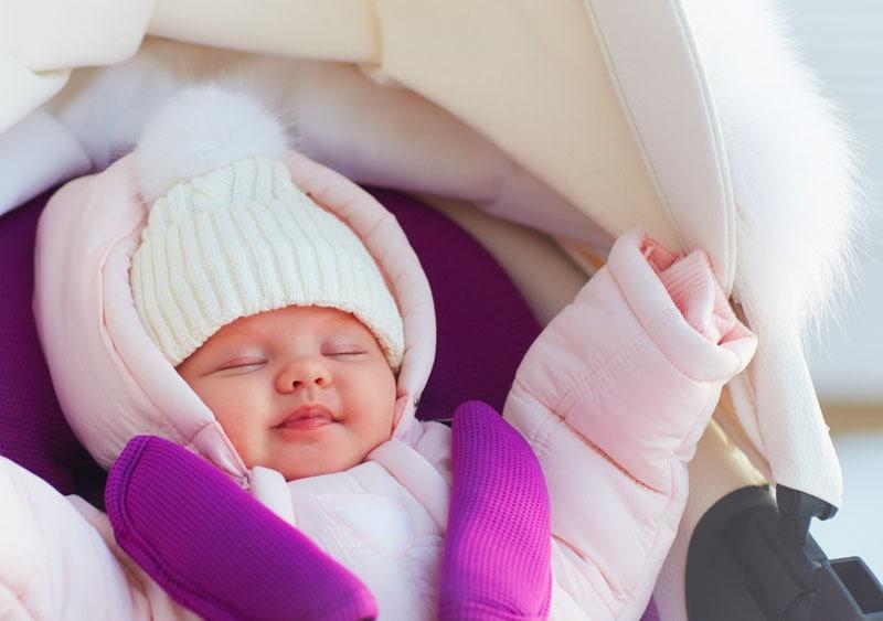 schönes lächelndes Baby in Winterjacke und Hut