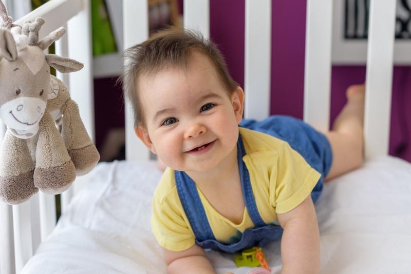 süßes Baby mit dem Gesicht nach unten in einer weißen Krippe liegend