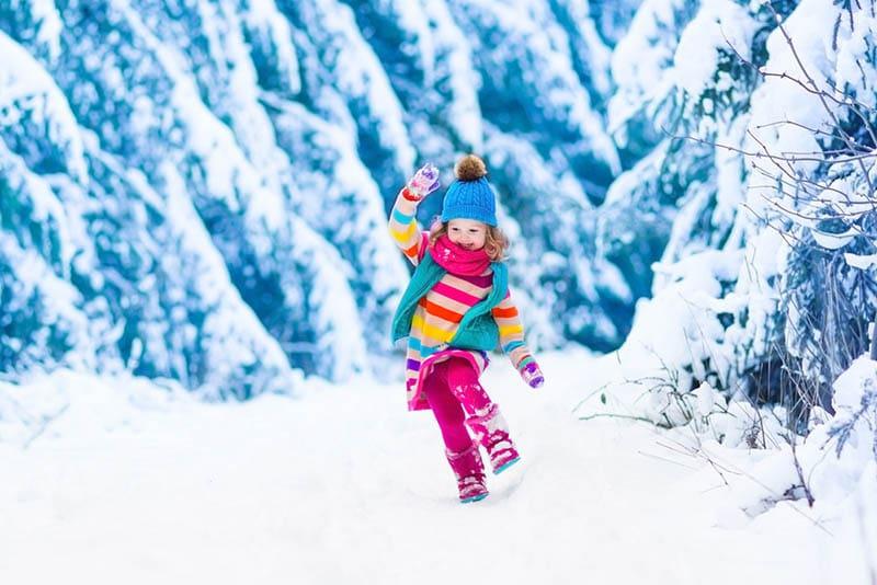 süße lächelnde Mädchen trägt bunte Kleidung auf Schnee