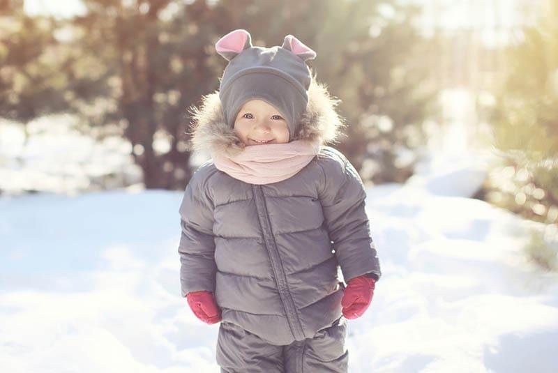 süßer kleiner Junge steht auf dem Schnee
