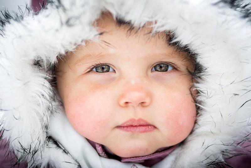 süßes Baby Junge mit dicken Wangen trägt Wintermütze
